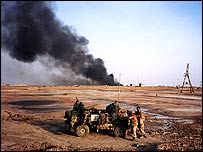 Troops in desert with oil ablaze   BBC