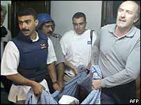 Journalists carry wounded colleague from Baghdad's Palestine Hotel, 8 April 2003