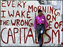 A college student leans against a wall painted with anti-capitalism graffiti, Mumbai
