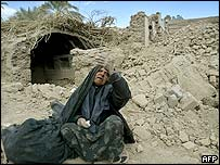 An elderly woman sits amid the ruins in Bam
