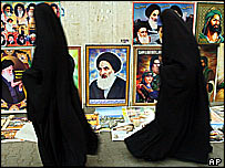 Shia women walk past images of Ayatollah Ali Al-Sistani in Basra