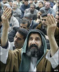 A Shia man takes part in Friday prayers