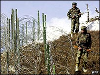 Indian troops patrolling along part of the new barbed wire fence in Kashmir