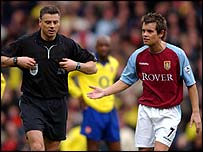 Referee Mark Halsey is confronted by Villa midfielder Lee Hendrie