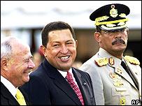 Venezuela's President Hugo Chavez (c) and former Defence Minister Jose Prieto (l) with new Defence Minster Jorge Garcia Carneiro (r)