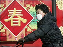 A masked cyclist passes lunar new year decorations in Beijing