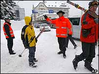 A policeman shows the way to a group of skiers in Davos