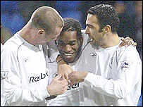 Jay-Jay Okocha is congratulated by Kevin Nolan and Stelios Giannakopoulos