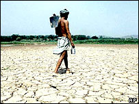 Farmer in dried-up lake bed