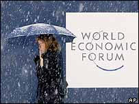A woman walks past a WEF sign