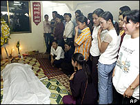 Cambodian union members grieve in front of the body of prominent labor leader Chea Vichea