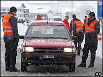 Policemen and security guards check a car on its way to Davos