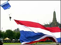 A skydiver with the Thai flags lands near the Grand Palace in Bangkok