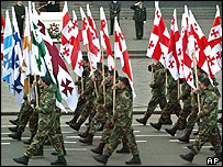 Soldiers carrying the new Georgian national and military flags parade