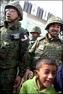Japanese advance troop commander Masahisa Sato (right) smiles to Iraqi children