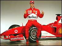 Michael Schumacher poses with the new Formula One Ferrari