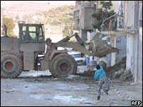 A Palestinian boy throwing a stone at an Israeli army bulldozer