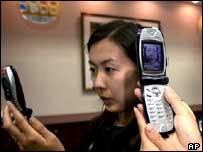 Staff at Japanese mobile firm NTTDocomo check new 3G phones