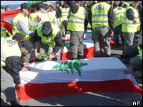 Hezbollah defence workers cover the coffins of Lebanese guerrillas