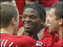 Louis Saha is congratulated by his new Manchester United team-mates
