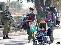 A settler family passes a soldier in Netzarim settlement in Gaza