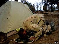 A Muslim member of the US army prays in Afghanistan