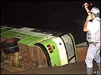 A police officer at the scene of a bus which crashed after being swept off a Sao Paulo state road by heavy rains, on 9 January