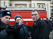 Russian Interior Ministry officers direct injured man to safety by scene of blast
