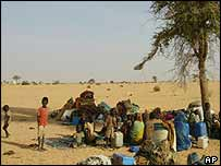 Refugees wait under a tree in Tine at the end of January