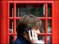 Man using mobile outside phone box, PA