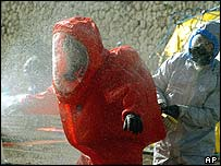 Firefighters in protective suits at the main train station in Piraeus
