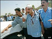 An injured officer is led away by colleagues after an attack in Baghdad