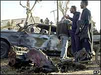 Iraqis stand near destroyed cars, 10 February 2004