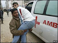 A Palestinian carries a wounded man in Gaza City