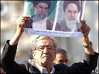 Iranian man holds picture of the late Ayatollah Khomeini [right] and Iran's Supreme leader Ayatollah Ali Khamenei [left]