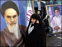 Iranian woman with pictures of former supreme leader Ayatollah Khomeini and current supreme leader Ali Khamenei