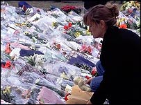 A mourner places flowers for Diana, Princess of Wales at Kensington Palace