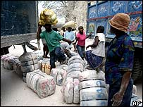 Residents of St Marc carry their belongings as they walk around a freight container and vehicles that form a barricade across the main road that connects northern Haiti and Port-au-Prince