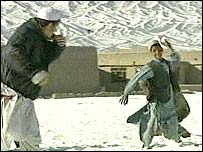 A young boy throws a snowball at ex-Guantanamo inmate Naqibullah