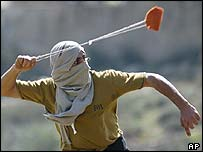 A Palestinian uses a slingshot to hurl a stone at Israeli forces
