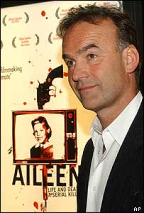 Director Nick Broomfield in front of a poster for Aileen: Life and Death of a Serial Killer