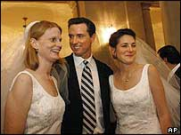 San Francisco Mayor Gavin Newsom stands between newlyweds