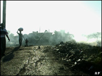 Haitians walk past burning rubbish near the port in downtown Cap-Haitien