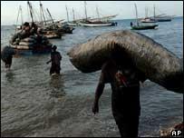 Hombre carga saco de carbón que llegó a Gonaives