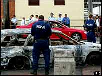 Sydney police inspect a burnt out car