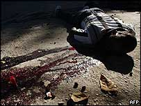 A man lies dead in a pool of blood on a street in Port-au-Prince