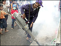 An Indonesian Health Ministry worker sprays insecticide in Jakarta