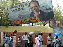 Haitians walk past a crooked billboard of President Aristide