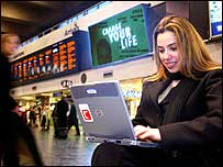 Woman using wireless laptop in a station