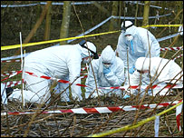 Forensic officers examine the riverbank next to the River Kent, Cumbria
